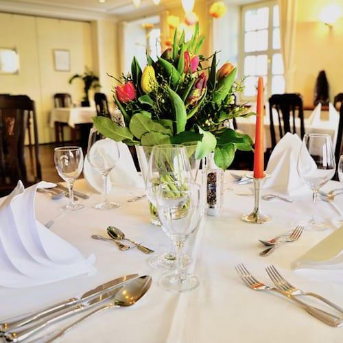 Gedeckter Tisch mit frischen Blumen im Restaurant Post