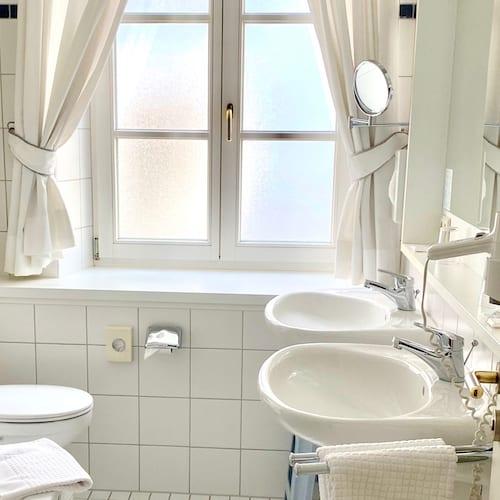 Bad im Doppelzimmer weiß und lichtdurchflutet